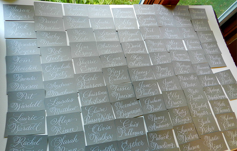Escort cards drying in my studio. I love the white ink on gray stock.